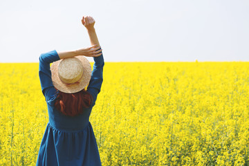 Wall Mural - girl walking in a field of yellow rapeseed