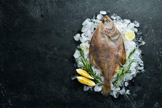 Raw flounder fish with spices. Seafood on a black stone background. Top view. Free copy space.