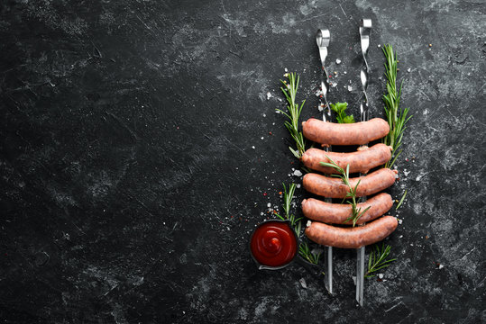 Raw Pork sausages with rosemary and vegetables. Top view. Free space for your text.