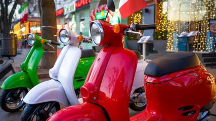 Fotorolgordijn Scooter Retro vintage scooters stand near an Italian restaurant. Modern personal transport.