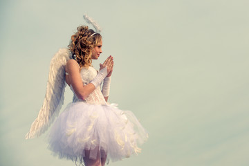 Angel child girl with curly blonde hair - Innocent girl concept. Teenager Cherub Cupid. Child with angelic character. Sweet angel girl. Pray. Angel wings baby pray. Teen angel.