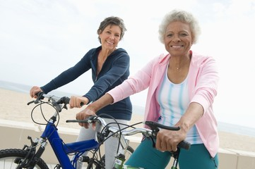 Portrait of happy senior multiethnic female friends riding bicycles together