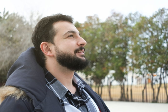 Bearded man profile in autumn image with warm clothing in outdoors park, smirking