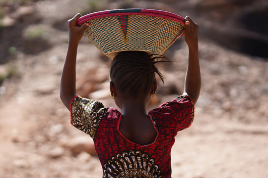 Candid Picture of Ethnic African Schoolgirl with Colorful Shirt and Basket