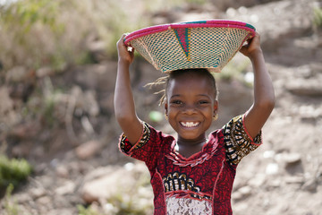 Body Shot of Cute African Young Girl Carrying Food Basket and Blurred Background Fotomurales