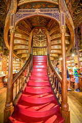 Oporto, Portugal - August 13, 2017: large wooden staircase with red steps inside Library Lello and Irmao, one of the world's most beautiful libraries in historic center, famous for Harry Potter film.