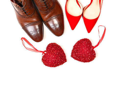 Valentines day concept with man and woman shoes with two red hearts on white background, isolated.