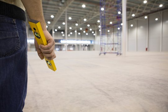 Manual Worker Holding Spirit Level In Warehouse