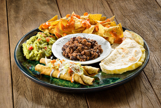 A tex-mex plate. Nachos with melted cheddar cheese on top, guacamole, burritos, quesadilhas and chili with meat. On a wooden table.