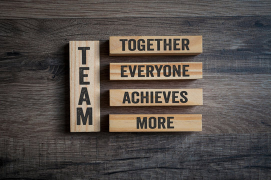 Wooden pieces with Team - Together everyone achieves more on wooden background
