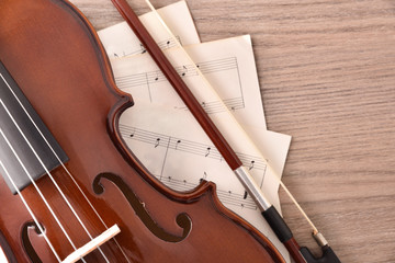 Violin body and bow with sheet music on wood table