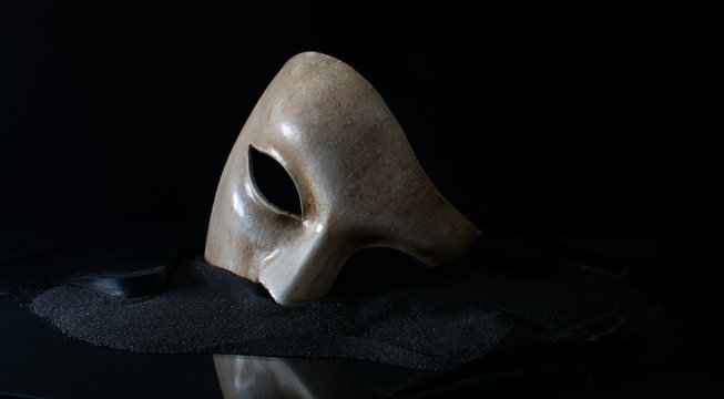White opera mask on the sand
