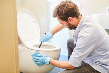 Hausmann beim WC putzen für Emanzipation Fototapete