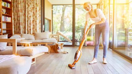 Frau mit Staubsauger und Hund im Wohnzimmer Fototapete