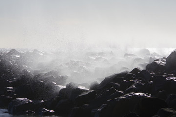 Recess Fitting Gray traffic A field of rocks on the open California ocean shore being sprayed by splashing waves on a windy winter day