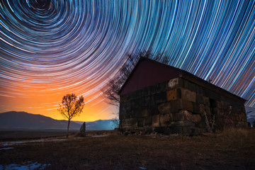 Beautiful night landscape, small church and star trails. The colorful star trails on the sky with orientation on the north star. Night time lapse photography. Fotomurales