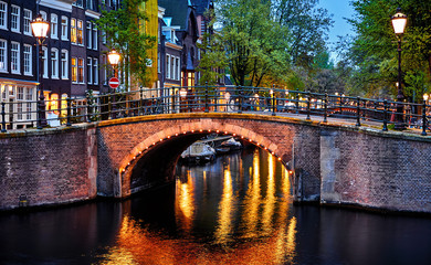 Fototapete - Amsterdam, Netherlands. Bridges with nighttime illumination over canals with water in Old town. Quarter with traditional dutch houses. Vertical evening landscape. Blue hour.