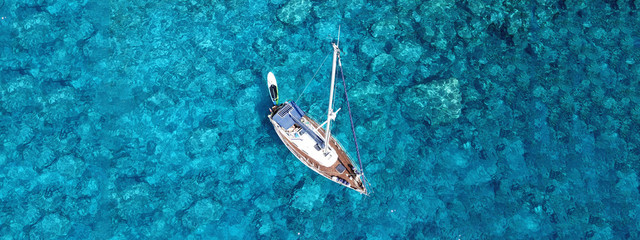 Aerial drone photo of luxury sail boat docked in tropical exotic bay with turquoise crystal clear sea