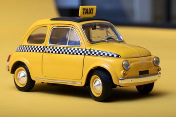 Yellow retro toy taxi on yellow background