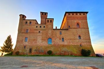 Golden hour view of Grinzane Cavour castle, historical landmark, village in Langhe region, Cuneo, Piedmont, Italy.