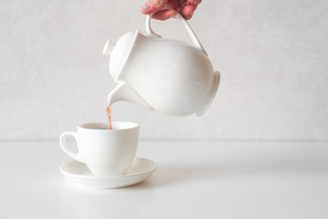Pouring fresh tea from white teapot into white cup