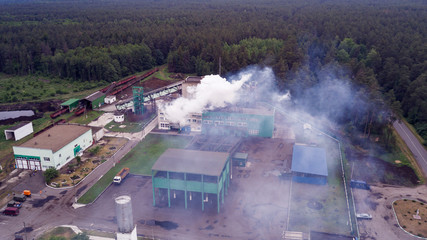 Fototapeta Aerial view. Industry, industry and ecology problem. Dark smoke of the peat plant polluties the environment.
