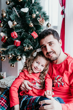 father and daughter at home wearing matching pajamas. christmas season