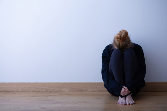 Sad teenager girl sitting curled up on the floor, copy space on empty wall