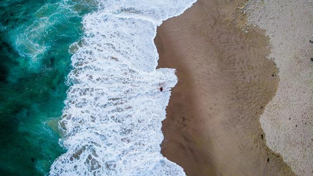 Aerial view of a man standing in a ocean foam in Laguna Beach, California, USA