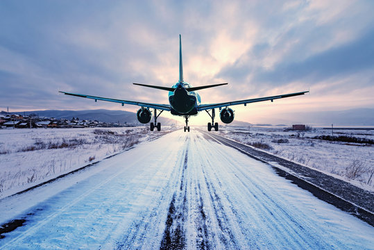 Landing of the passenger plane to the highway at winter evening time.