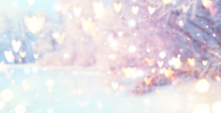 St. Valentine's Day winter blurred background with glowing hearts. Xmas trees with snow, holiday festive background. Widescreen backdrop. New year Winter art design with snowflakes. Nature scene