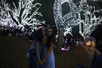 Women pose for a picture near Christmas lights decoration at Ibirapuera Park in Sao Paulo