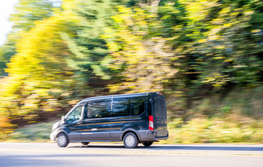 Black compact cargo business mini van running on the autumn road with trees on the side