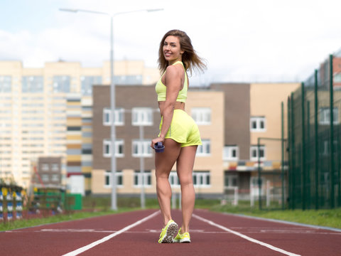 Female urban fitness. Caucasian smiling sexy woman with elastic band staying on jogging track outdoor, back view, selected focus.