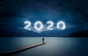 New year background, young man standing on a jetty in a lake and looking to the mountains under the dark sky with cloudy text 2020