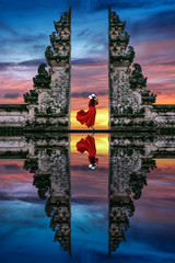 Ingelijste posters Bedehuis Young woman standing in temple gates at Lempuyang Luhur temple in Bali, Indonesia.