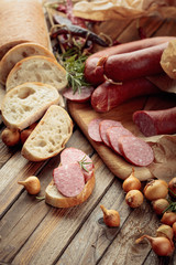 Fototapete - On a old wooden table sausage with bread, rosemary, onion and pepper.