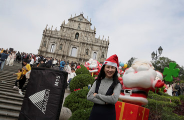 A woman poses for a photo next to the Christmas decorations as visitors tour the Ruins of St. Paul's in the historic centre of Macau