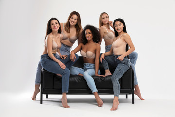 Group of women with different body types in jeans and underwear on sofa against light background