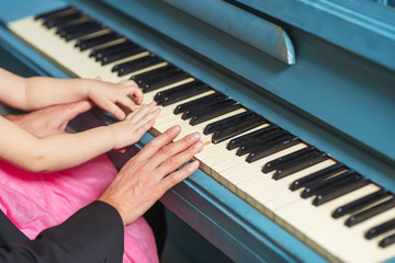 Men's and children's hands on the piano keys. Dad and little daughter play the piano. Hands on the...