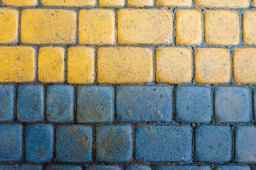 yellow and blue cobbles of pavement texture. stone masonry floor covering. top view of wet grungy background