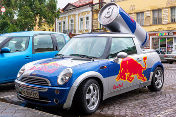 Red Bull mini cooper publicity car with a can of energy drink behind. fancy car tuning used for promotion. wet advertisement vehicle after the rain
