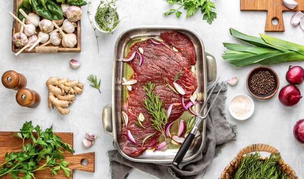 Raw flank steak marinated in a spicy mix with herbs, top down view