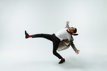 Young caucasian man moving flexible on white studio background. Male model in office attire bending over, avoiding something, catched in motion and action. Looks angry, scared, fighting. Emotions.