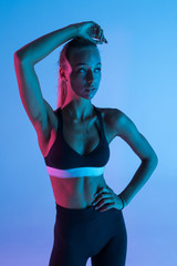 Young fitness woman isolated on purple background