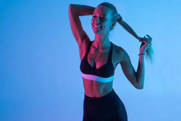 Young pretty fitness woman make ponytail isolated on purple light background