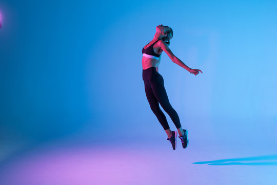 Sporty young woman fitness jumping isolated on purple light background