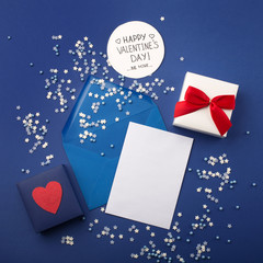 Empty card with blue envelope, gift and red heart on classic blue background.