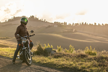 Man on his motorbike standing on a country road on hills landscape at sunset. Tuscany, Italy. Wall mural