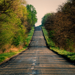 landscape in hilly countryside with old asphalt road.